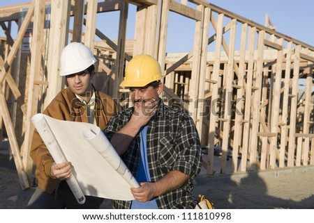 Construction workers discussing above holding blueprints - stock photo