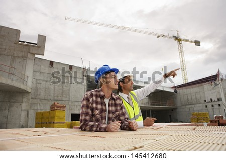 Construction workers discussing job at building site - stock photo