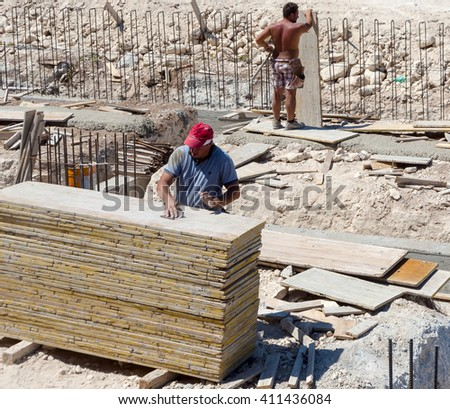 Construction workers fabricating ground beam timber formwork at construction site - stock photo