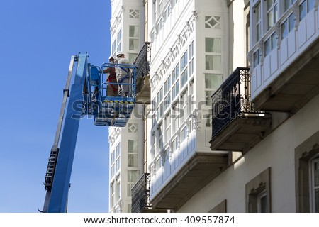 construction  workers in bucket of  crane vehicle for restore the facade of antique building - stock photo