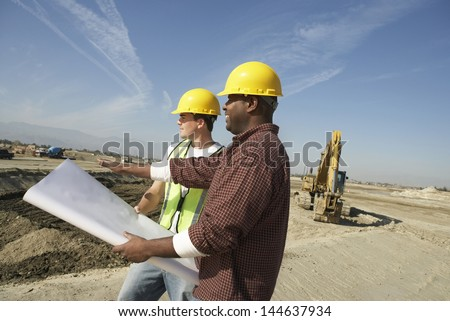 Construction workers in hard hats looking at plan on site - stock photo