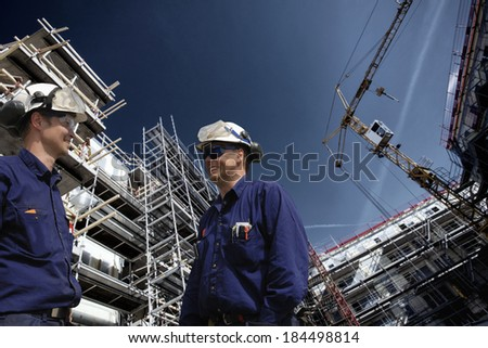 construction workers inside large building site, super-wide perspective - stock photo
