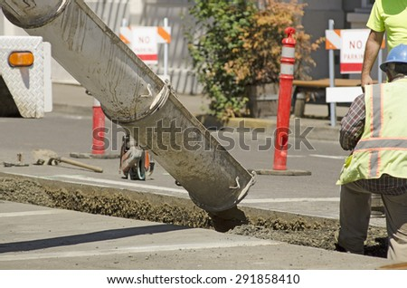 Construction workers installing new utilities pour concrete to cover and stabilize a trench with water and sewer pipe - stock photo