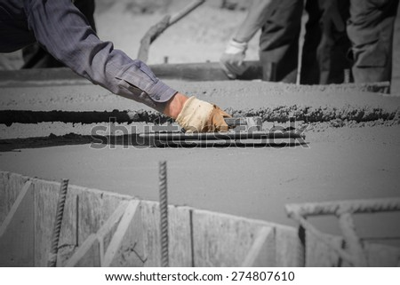 Construction workers leveling concrete pavement. - stock photo
