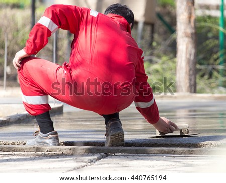 Construction workers leveling concrete pavement.