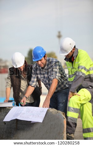 Construction workers looking at site plans - stock photo