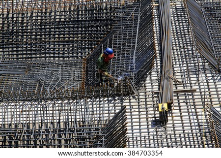 Construction workers making reinforced concrete frame in the construction site - stock photo