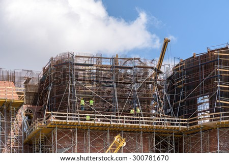 Construction Workers On Building Construction Site Scaffold - stock photo