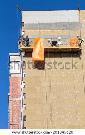 Construction workers plastering facade of high-rise building - stock photo