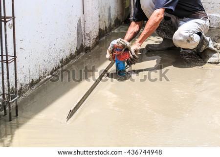 Construction workers pouring concrete, Leveling concrete with trowels, mason hands spreading poured concrete. Selective focus.  - stock photo