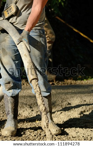 Construction workers pumping concrete on a sidewalk project in a local park - stock photo