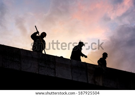 Construction workers silhouette in sunset - stock photo
