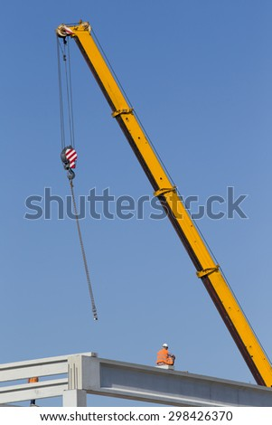 Construction workers sitting on concrete beam on height and waiting crane to lift truss for installation