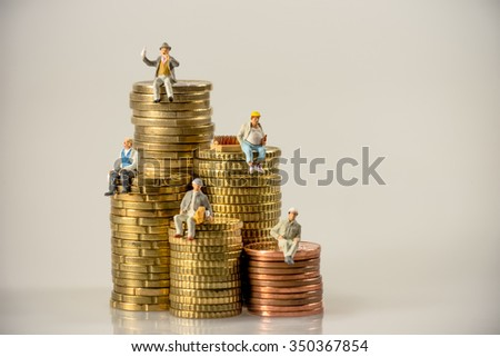 Construction workers sitting on money coin piles. Macro photo - stock photo