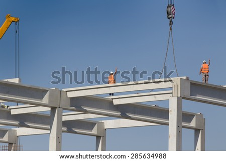Construction workers standing on concrete beam on height and placing truss lifted by crane - stock photo