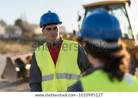 Construction workers talking outdoors near to excavator machine