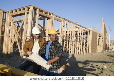 Construction workers with blueprint - stock photo