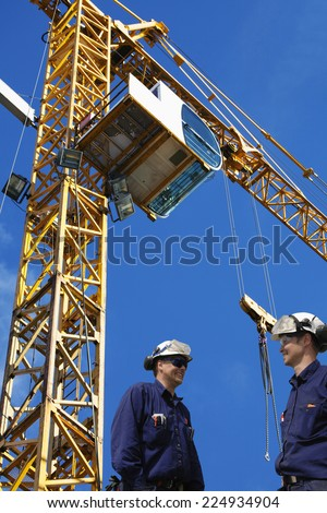 construction workers with tall mobile crane in the background - stock photo