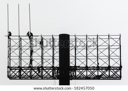 Construction workers working on scaffolding - stock photo