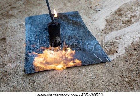 construction works: propane blow torch flame and melting insulation material during waterproofing works basement concrete wall - stock photo