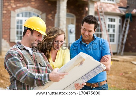 Construction: Young Couple Look At Home Plans with Builder. - stock photo