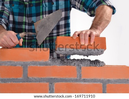 Constructor hand holding a brick and building a wall. - stock photo