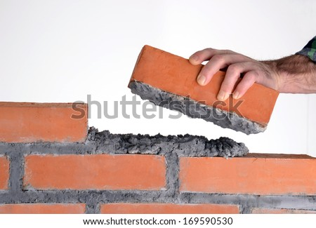 Constructor hand holding a brick and building a wall.building brick block wall - stock photo