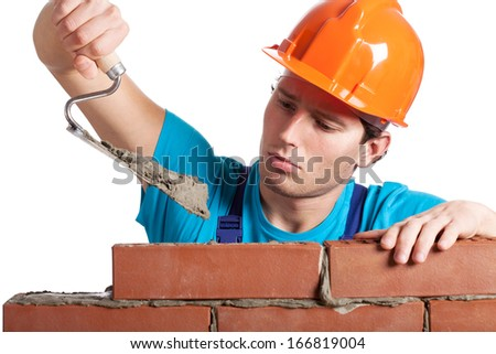 Constructor with putty knife building a brick wall - stock photo