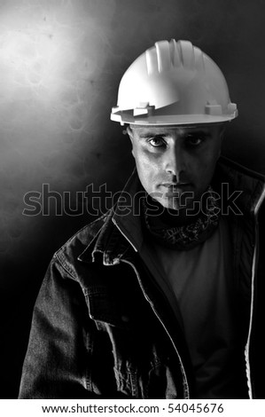 Constructor worker posing in a dark background - stock photo