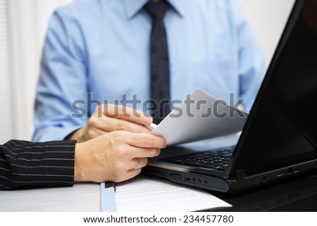 Consultant and client are working with documents and laptop on office desk - stock photo