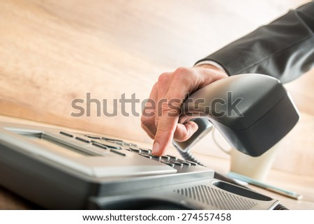 Consultant holding the receiver of a corded desk phone while dialing, in the office. - stock photo