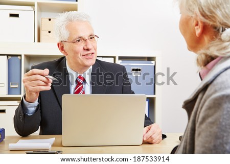 Consultant in bank making financial proposal to senior customer - stock photo