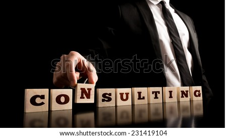 Consultant in Black Business Suit Arranging Small Wooden Pieces with ConsultingText on Black Background. - stock photo