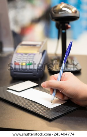 Consumer signing on a sale transaction receipt with Credit Card Machine and Barcode Scanner in Background - stock photo