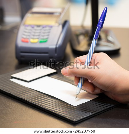 Consumer signing on a sale transaction receipt with Credit Card Machine in Background - stock photo