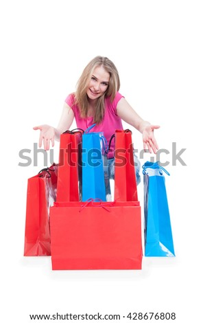 Consumerism and sale concept with cheerful woman showing colorful shopping bags isolated on white background with copyspace - stock photo