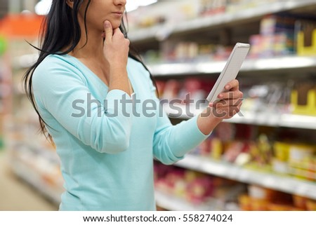 consumerism, shopping and people concept - woman with notebook at grocery store or supermarket