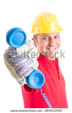 Contact construction company concept with builder holding phone - stock photo