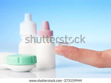 contact lens on finger and eye drops - stock photo