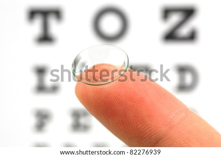 Contact lens on finger and snellen eye chart. The eye test chart is shown blurred in the background. - stock photo