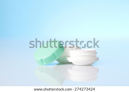 contact lenses case on blue background - stock photo