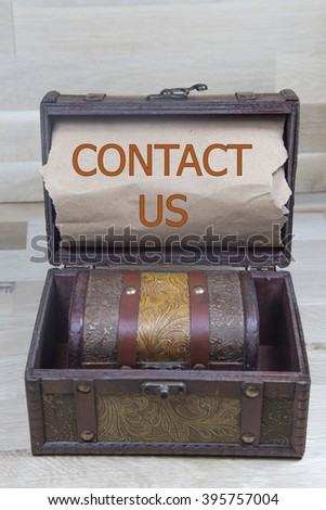 contact us is written on the brown torn paper in the treasure box