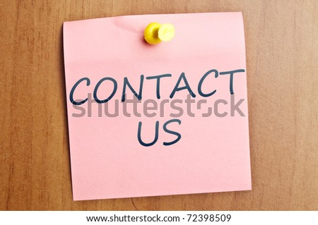 Contact us  post it on wooden wall - stock photo