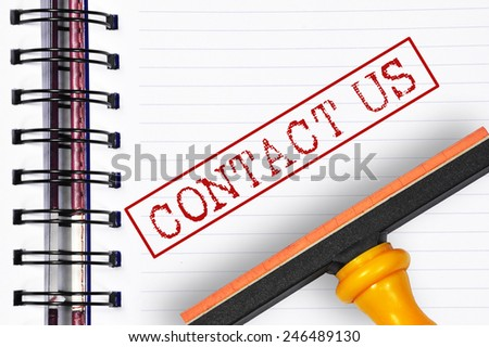 Contact us rubber stamp on the note book - stock photo