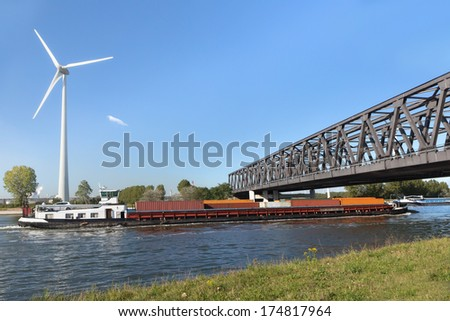 Container barge sailing under the Noordland bridge on the Scheldt-Rhine canal which connects the 2 great ports of Antwerp and Rotterdam - stock photo