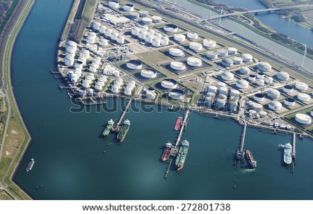 container boats in the europoort harbour at the jetty  wit oil storange tanks and the calland canal - stock photo