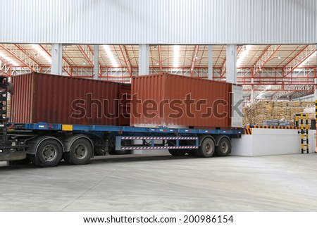 Container box on truck at loading dock shipping industry warehouse  - stock photo