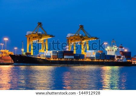 Container Cargo freight ship with working crane bridge in shipyard - stock photo