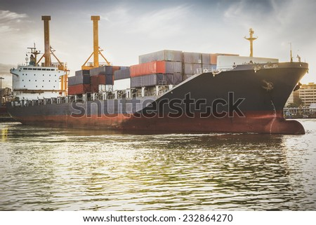 Container Cargo freight ship with working crane bridge in shipyard at befor sunrise.