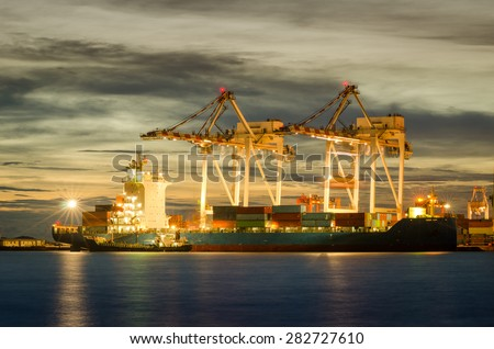 Container Cargo freight ship with working crane bridge in shipyard at dark